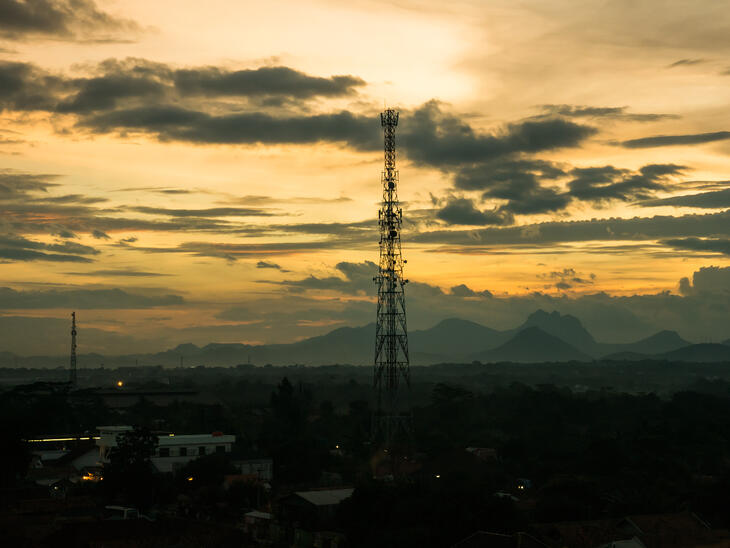 A cell tower with mountains and the setting sky in the background.