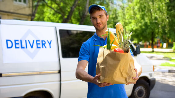 A delivery person standing outside of a white delivery truck holding a paper bag filled with food items.