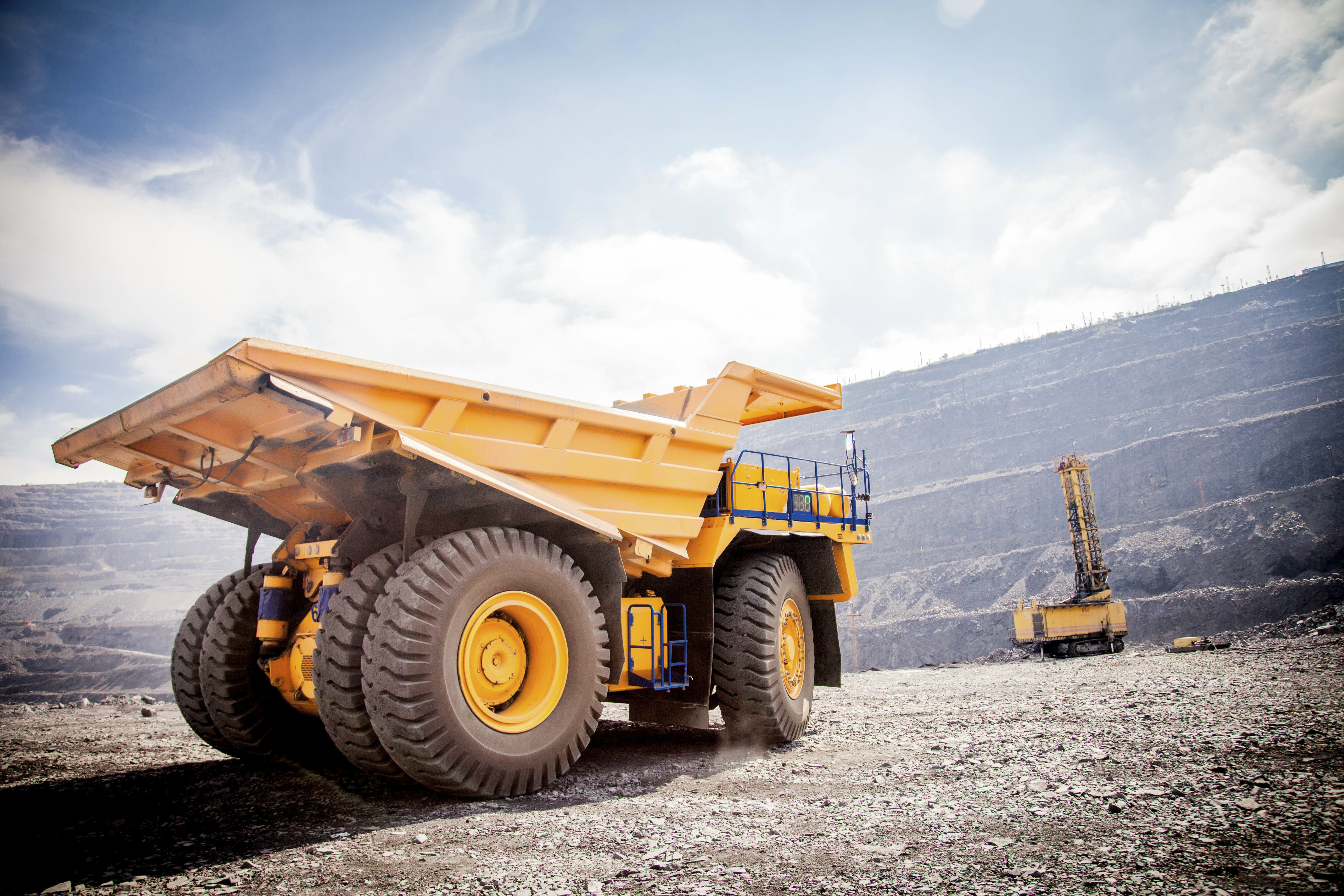 A mining site during the day with a yellow vehicle in the foreground and a drill in the background.