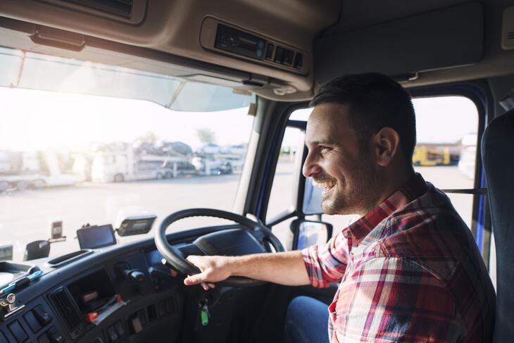 A smiling truck driver wearing a red shirt driving a truck during the day.