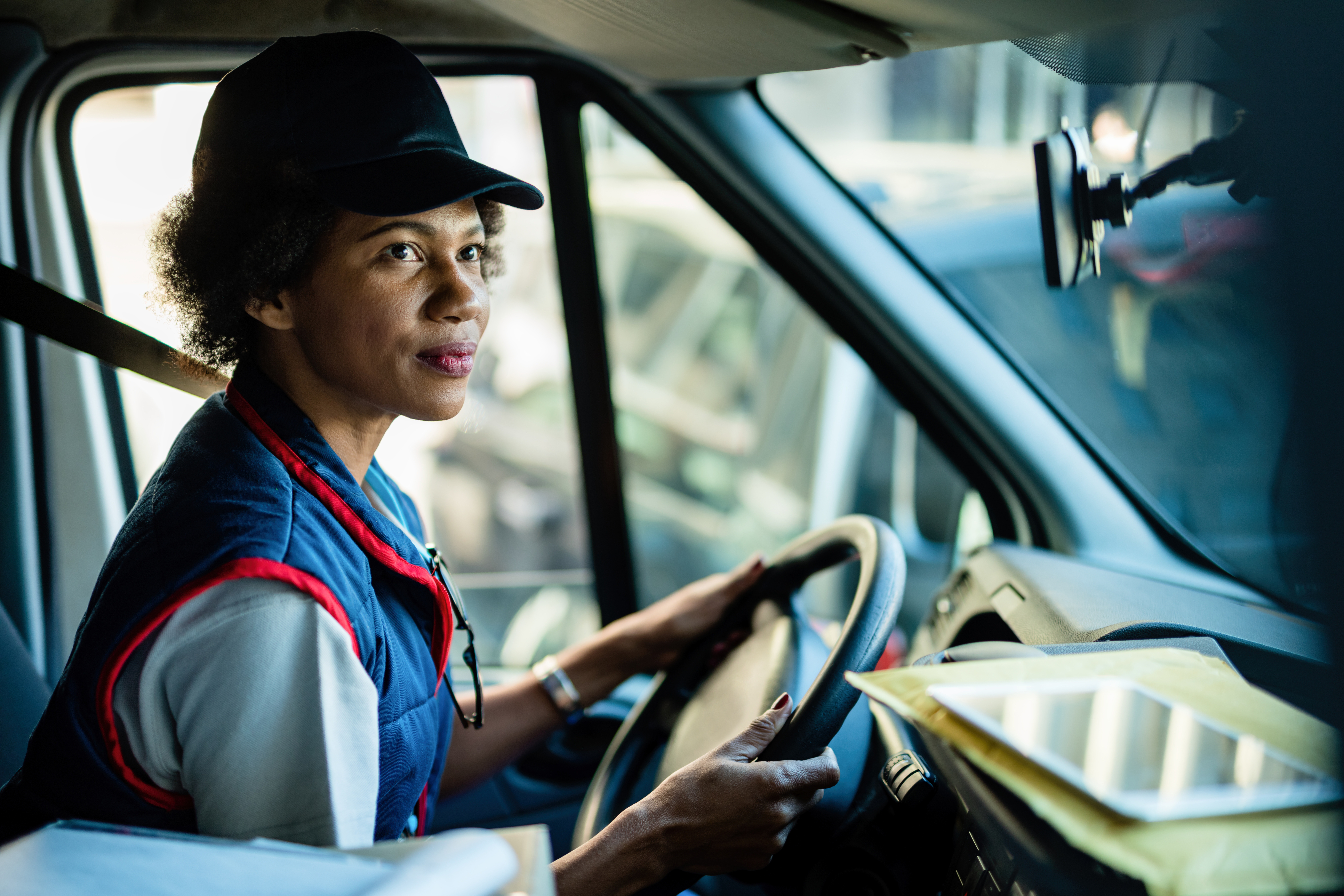 A woman wearing a black hat and a blue and red vest is driving a truck while holding the steering wheel with two hands and looking in the rear-view mirror.