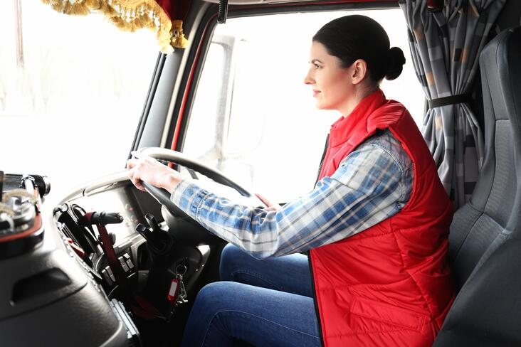 A woman wearing a red vest is driving a truck while holding the steering wheel with two hands.