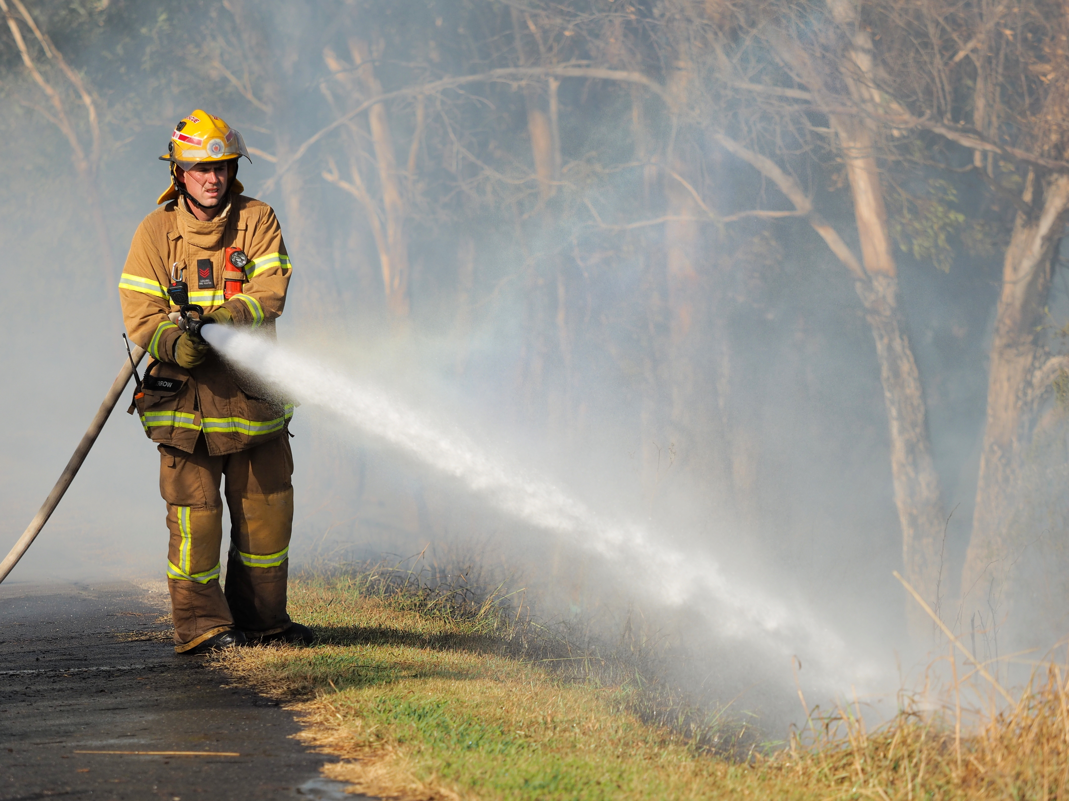 Fireman fighting fire with hose