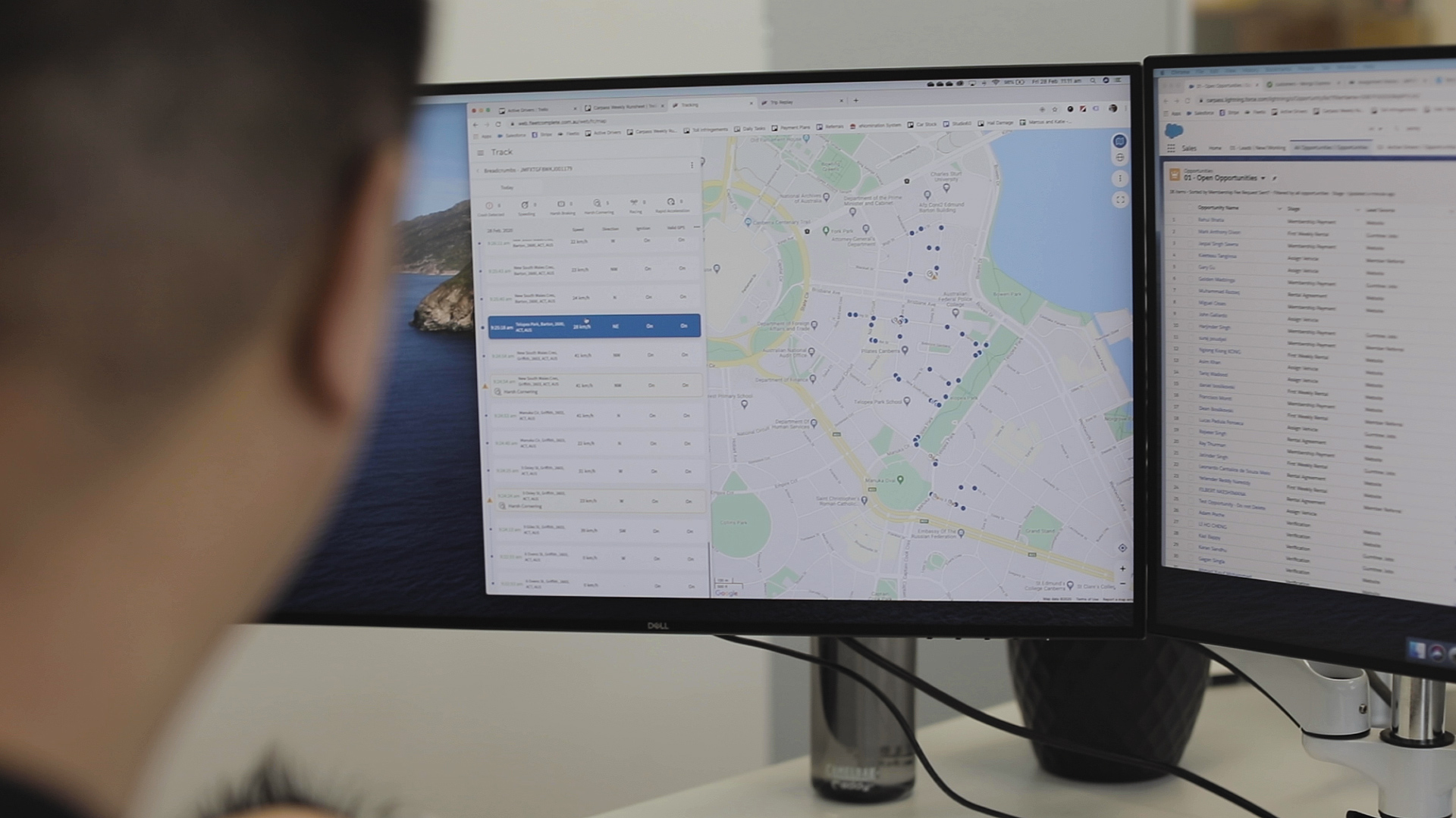 Man sitting in front of a computer screen with Fleet Complete tracking map.