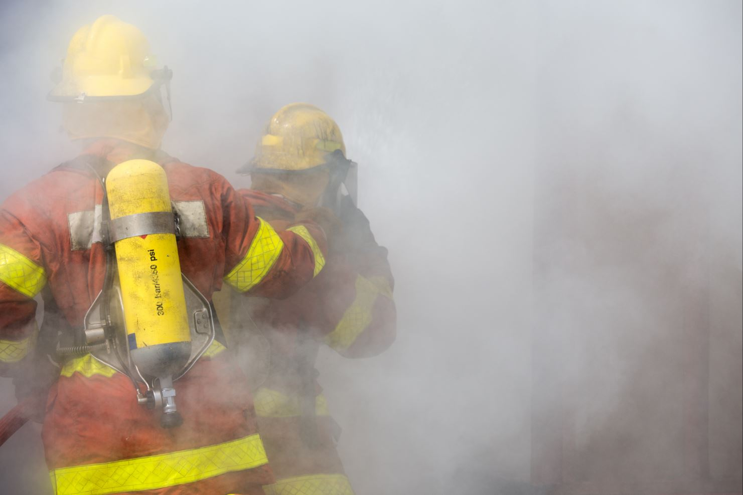 Firefighters walking into the cloud of smoke.