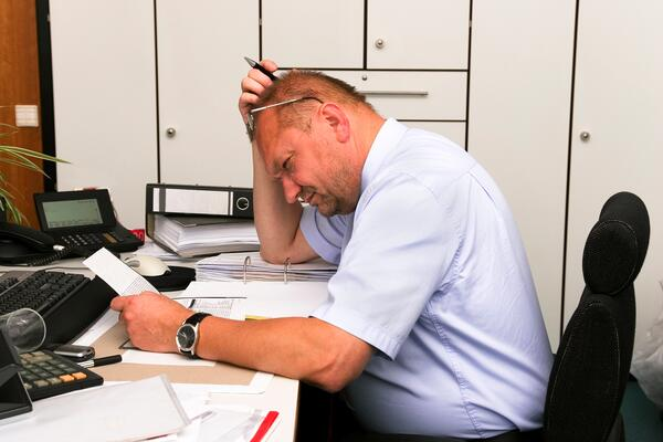 A male fleet manager squinting at a piece of paper that he's holding in his hand at a work desk.