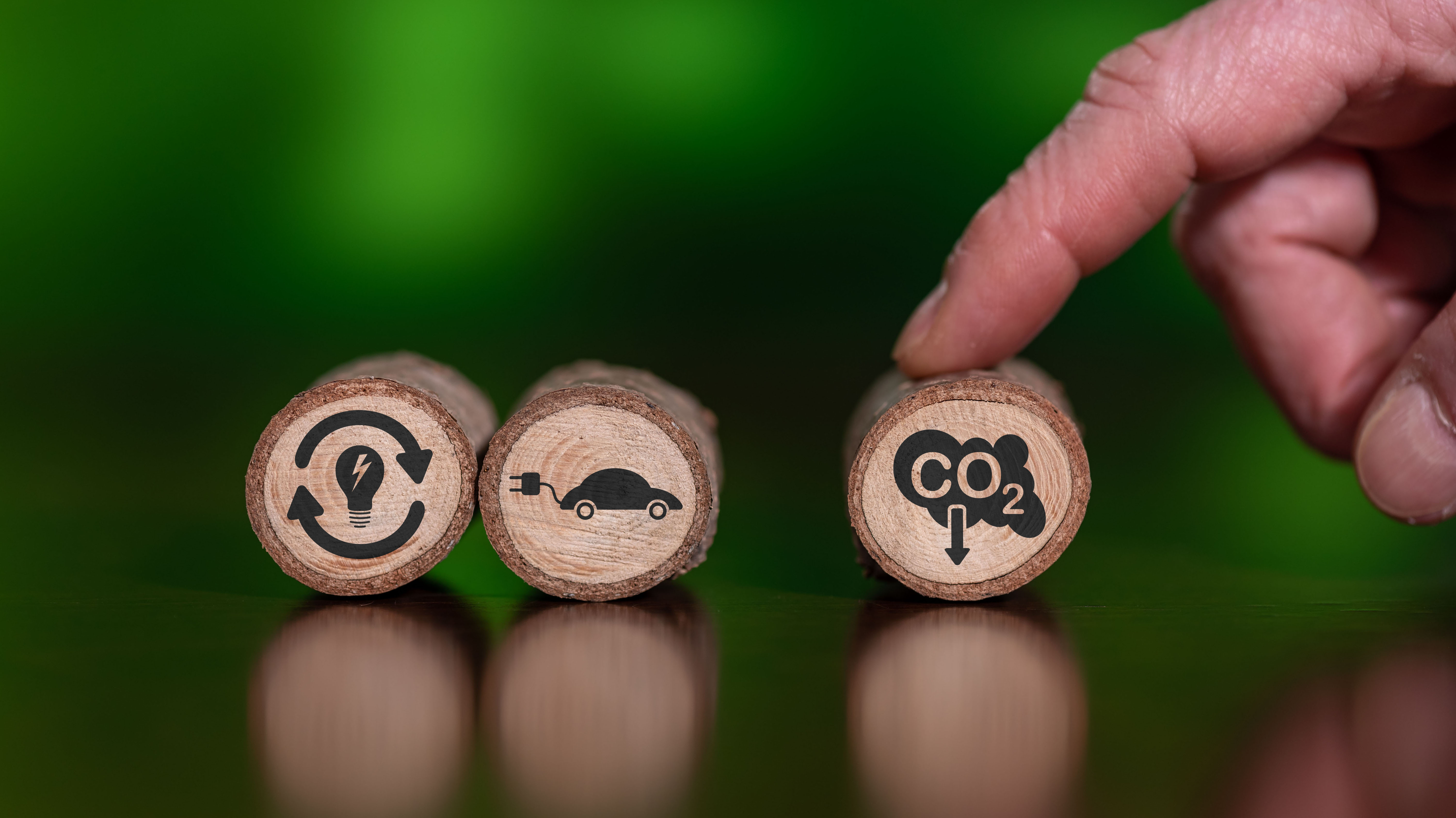 Three symbols representing sustainable energy, electric vehicles, and reducing CO2 emissions.