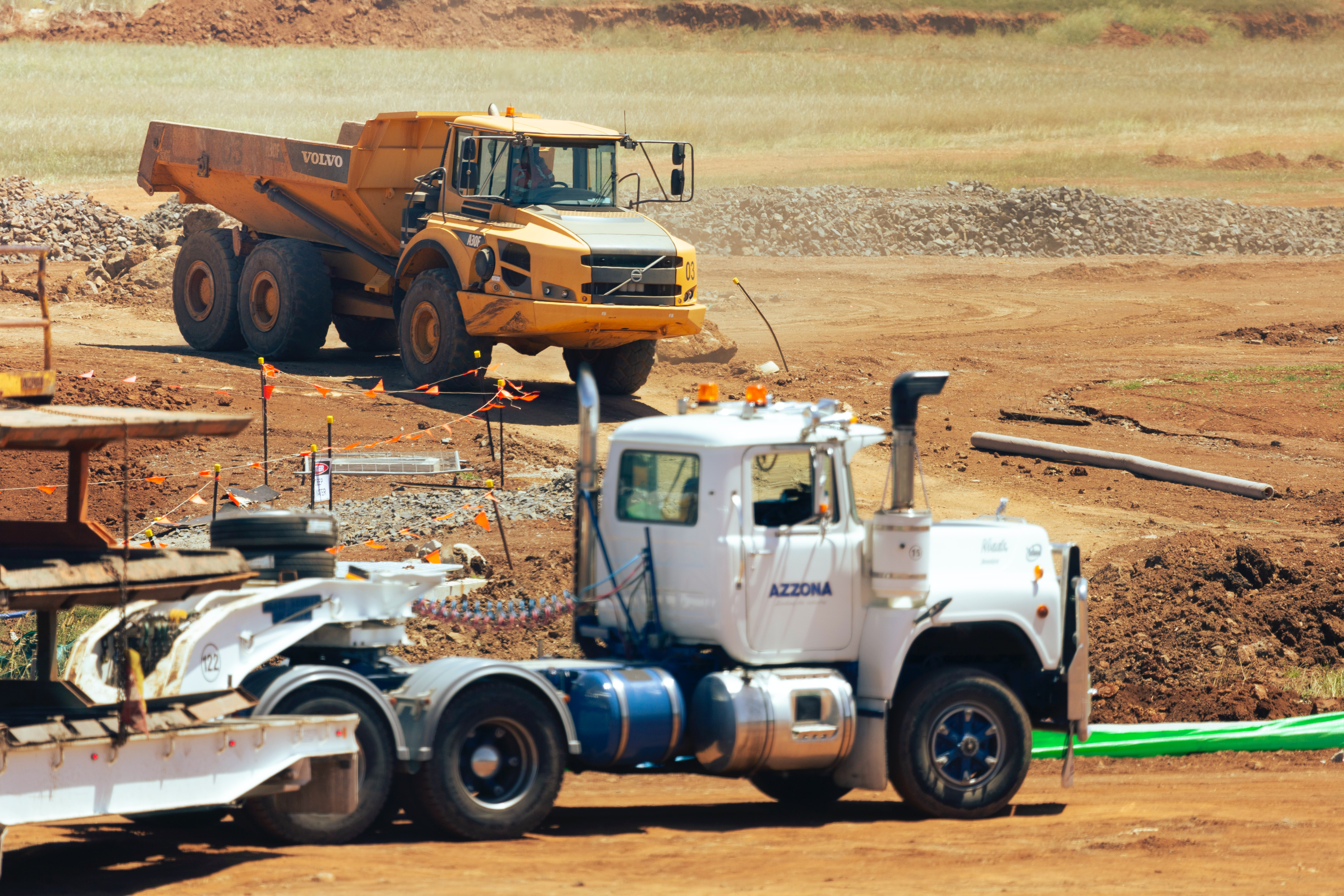 Large yellow and white trucks at a construction site in Australia..