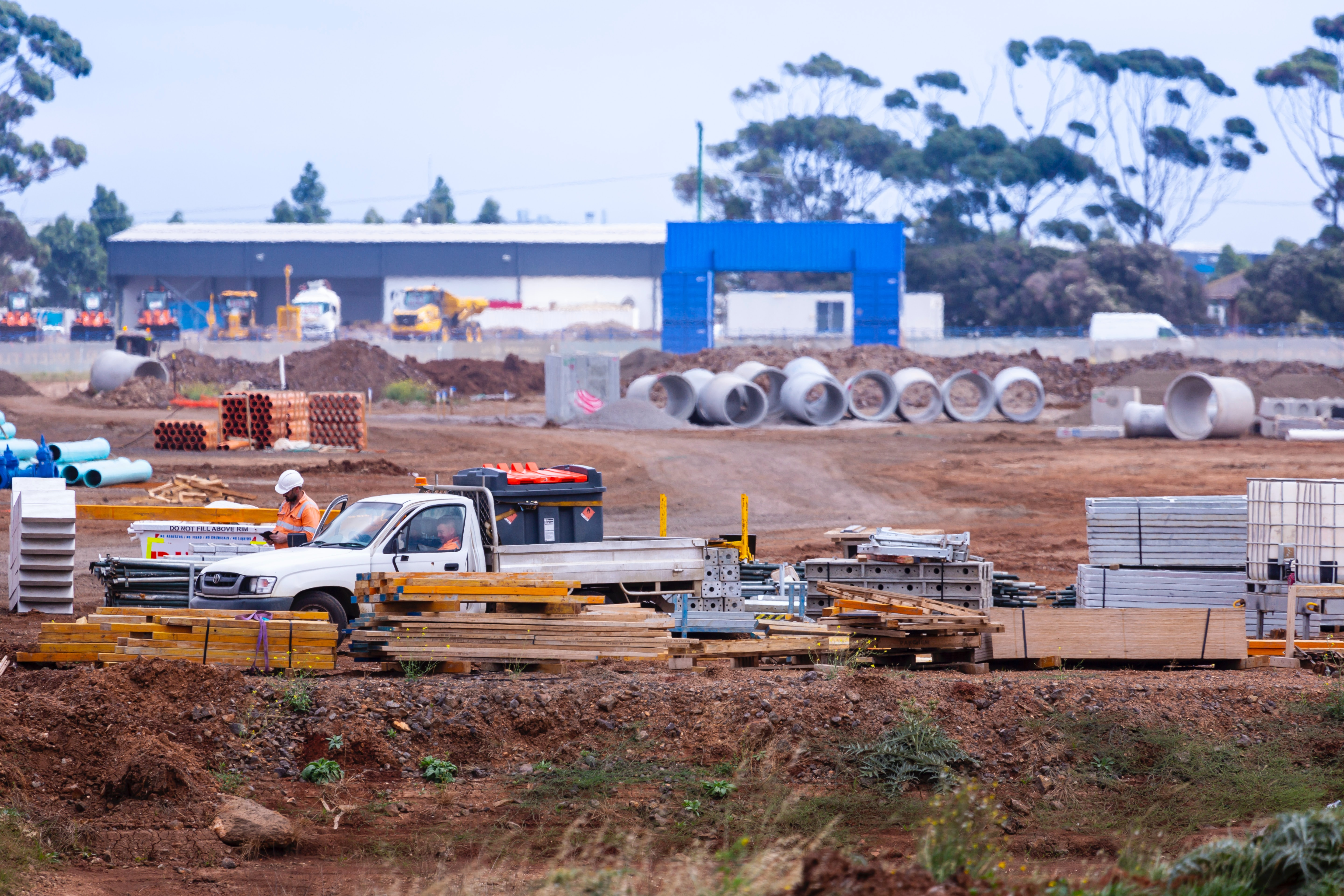 Vehicle parked at a construction site in Australia, with a construction worker next to it wearing a hardhat and an orange reflective jacket.